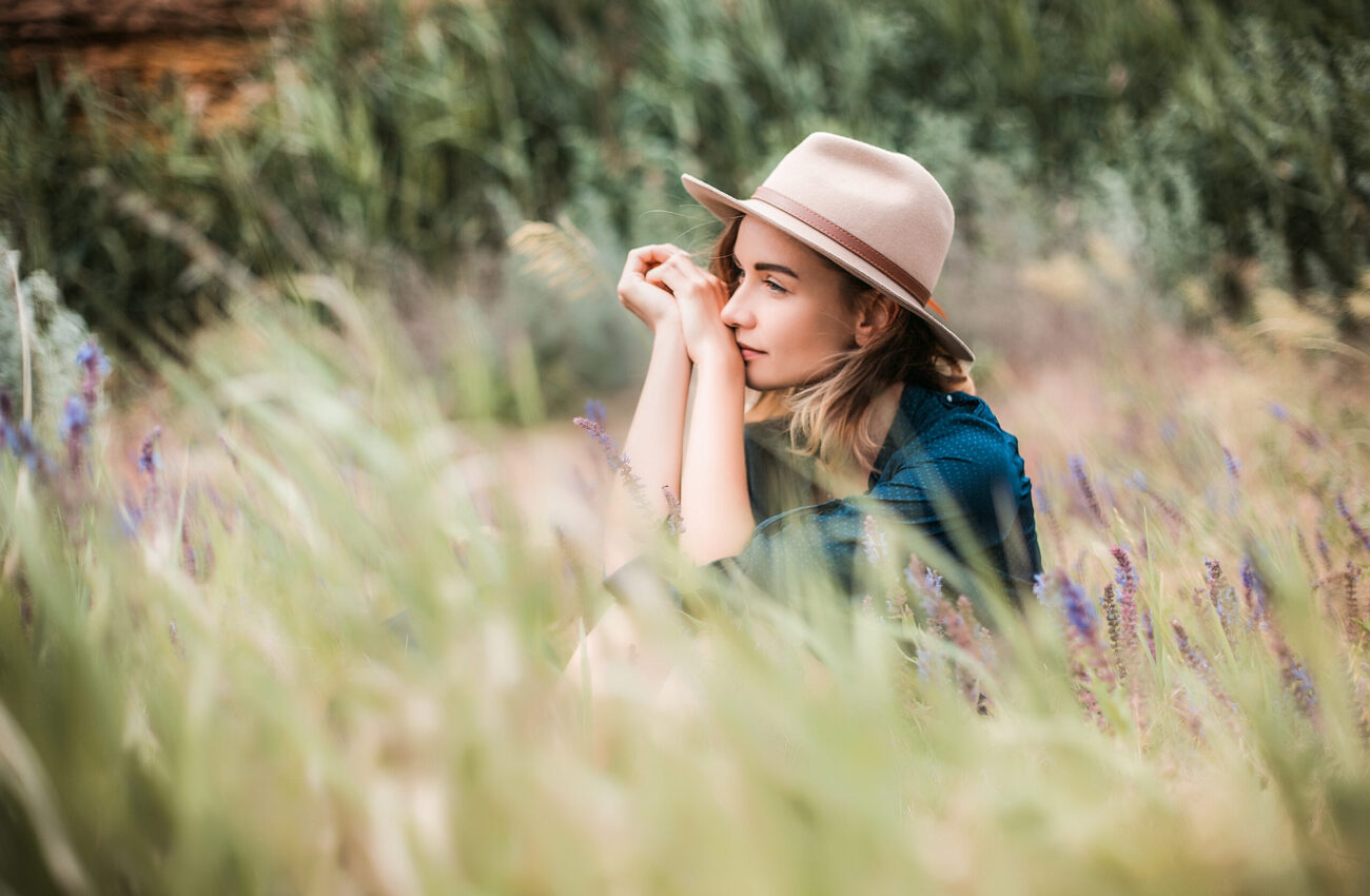 Summer,Portrait,Of,Young,Hipster,Woman,Sitting,In,A,Grass